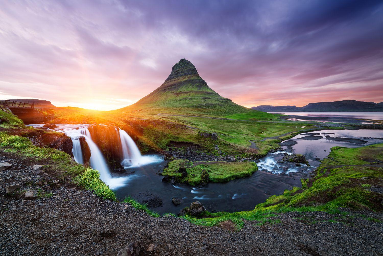 Wasserfall und Berg vor wunderschönem Abendhimmel. Thema: Reise nach Island