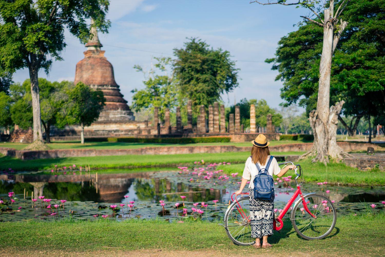 Junge Frau steht mit einem Fahrrad vor einem alten Tempel, der von Bäumen und einem Teich umrandet ist. Thema: Nachhaltiger Urlaub