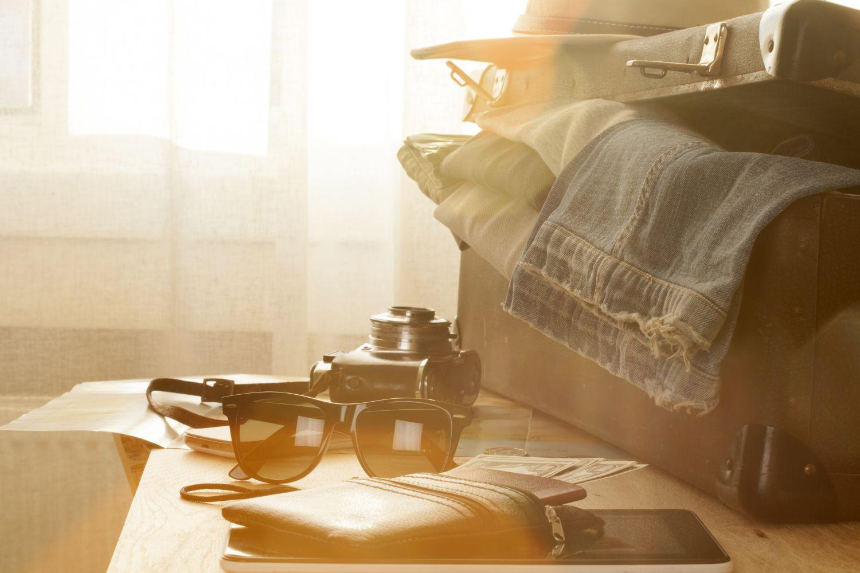 Sonnenbrille, Kamera und geöffneter Koffer auf Tisch